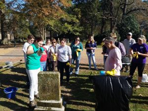 Volunteers gather around a grave during our cemetery preservation workshop.